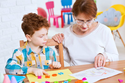 Young boy learning new words playing with colorful letters with his teacher